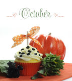 Beautiful orange Halloween theme cupcake with seasonal flowers and decorations for the month of October. With sample text or copy space for your text here stock photo