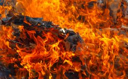 Close up to the belly off the fire. Beautiful orange lames mask detail of the burning waste.  Red hot ash and searing heat  - powerful force of nature Royalty Free Stock Images