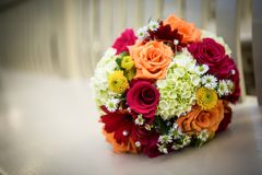 Orange, yellow, white wedding bouquet. Beautiful orange, red, and yellow bouquet loaded with daisies and roses on a bench with shallow depth of field Stock Photography
