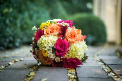 Orange, yellow, white wedding bouquet. Beautiful orange, red, and yellow bouquet loaded with daisies and roses on a bench with shallow depth of field Stock Photos