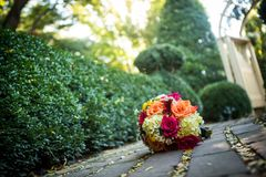 Orange, yellow, white wedding bouquet. Beautiful orange, red, and yellow bouquet loaded with daisies and roses on the ground with shallow depth of field Royalty Free Stock Images