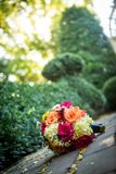 Orange, yellow, white wedding bouquet. Beautiful orange, red, and yellow bouquet loaded with daisies and roses on the ground with shallow depth of field Royalty Free Stock Photo