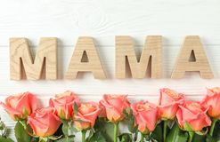 Beautiful orange roses and inscription Mom on white background. Space for text stock images