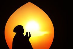 Beautiful orange silhouette of muslim praying at mosque Stock Photos