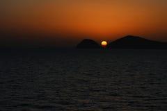 Beautiful orange sun between two mountais at the sunset time near the sea. Stock Photos