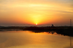 Beautiful orange sunrise and the sun and its reflection in the lake Stock Photo