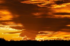 Beautiful orange sunset with a few clouds and sun rays. A beautiful orange sunset with a few clouds and sun rays royalty free stock photo