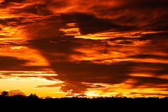 Beautiful orange sunset with a few clouds and sun rays. A beautiful orange sunset with a few clouds and sun rays royalty free stock image