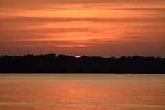 Beautiful orange sunset reflected on the calm water of the lake. Orange sunset reflected on the calm water in the lake with the sun almost totally hidden by the Royalty Free Stock Image