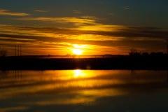 Beautiful orange sunset sky reflecting in lake.  Stock Photos