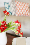 Beautiful orange tulips bouquet on wooden table in the living ro Stock Photography