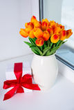 Beautiful orange tulips and gift box on a window sill Stock Images