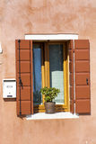 Beautiful orange window with pot flowers in Burano island (Venice, Italy) Stock Images