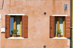 Beautiful orange windows with pot flowers in Burano island (Venice, Italy) Royalty Free Stock Images