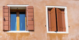 Beautiful orange windows with pot flowers in Burano island (Venice, Italy) Royalty Free Stock Photography