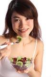 Beautiful oriental girl eating bowl of fruit Stock Image