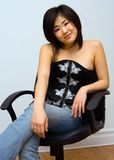 Beautiful Oriental woman. Sitting comfortable in a chair stock photos