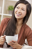 Beautiful Oriental Woman Drinking Tea or Coffee. A beautiful happy young Chinese Asian Oriental woman with a wonderful toothy smile drinking tea or coffee Stock Photo