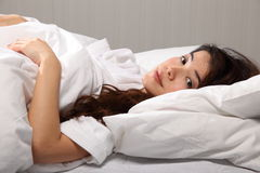 Beautiful oriental woman lying in bed eyes open Stock Photos
