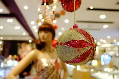 A beautiful ornament ball hanging from the building ceiling with blurred a woman mannequin stock image