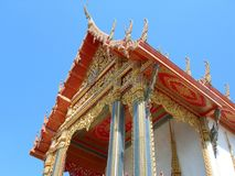An ornate roof of a Buddhist temple in Phetchaburi, Thailand. A beautiful ornate roof painted in gold and red and inlaid with colored glass in Phetchaburi Stock Photography
