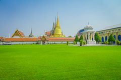 Beautiful outdoor view of green grass with a Wat Pho or Wat Phra Chetuphon in the horizont, `Wat` means temple in Thai. The temple is one of Bangkok`s most Royalty Free Stock Photography