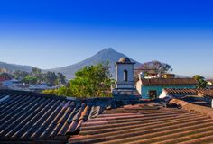 Beautiful outdoor view of rooftops of the building in Antigua city with agua volcano mountain behind in a beautiful. Sunny day and blue sky in Guatemala stock photos