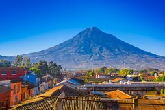 Beautiful outdoor view of rooftops of the building in Antigua city with agua volcano mountain behind in a beautiful. Sunny day and blue sky in Guatemala royalty free stock image