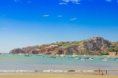 Beautiful outdoor view of some boats in the water with restaurants and hotels on pacific ocean beachfront scene San Juan. Del sur Nicaragua Royalty Free Stock Photo