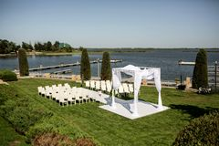 Beautiful outgoing wedding set up. Jewish Hupa  on romantic wedding ceremony , wedding outdoor on the lawn water view. Wedding. Decor. White wooden chairs on a royalty free stock photography