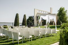 Beautiful outgoing wedding set up. Jewish Hupa  on romantic wedding ceremony , wedding outdoor on the lawn water view. Wedding. Decor. White wooden chairs on a stock photos
