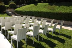 Beautiful outgoing wedding set up.Romantic wedding ceremony , wedding outdoor on the lawn water view. Wedding decor. White wooden. Chairs on a green lawn. White royalty free stock images