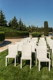 Beautiful outgoing wedding set up.Romantic wedding ceremony , wedding outdoor on the lawn water view. Wedding decor. White wooden. Chairs on a green lawn. White royalty free stock photos