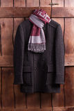 Beautiful overcoat with a scarf. Beautiful overcoat with a scarf hanging on a wooden fence Stock Photography