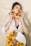 Woman with pizza. Beautiful overeat businesswoman lying with pizza pieces eating Royalty Free Stock Photo