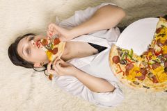 Woman with pizza. Beautiful overeat businesswoman lying with pizza pieces eating Stock Photos