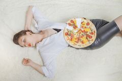 Woman with pizza. Beautiful overeat businesswoman lying with pizza pieces Stock Photos