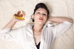 Woman with pizza. Beautiful overeat businesswoman lying with pizza pieces Stock Image