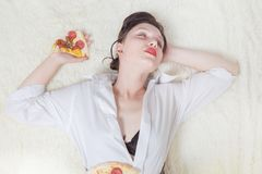 Woman with pizza. Beautiful overeat businesswoman lying with pizza pieces Royalty Free Stock Image