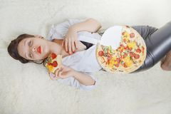 Woman with pizza. Beautiful overeat businesswoman lying with pizza pieces Royalty Free Stock Photo