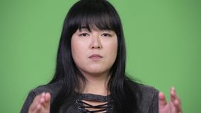 Beautiful overweight Asian woman covering ears as three wise monkeys concept. Studio shot of beautiful overweight Asian woman against chroma key with green stock video footage