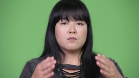Beautiful overweight Asian woman covering eyes as three wise monkeys concept. Studio shot of beautiful overweight Asian woman against chroma key with green stock video footage