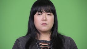 Beautiful overweight Asian woman covering mouth as three wise monkeys concept. Studio shot of beautiful overweight Asian woman against chroma key with green stock video