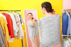 Beautiful overweight woman near mirror and rack Stock Photos