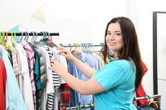 Beautiful overweight woman near rack with clothes Royalty Free Stock Photos