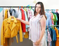 Beautiful overweight woman near rack with clothes Stock Photography