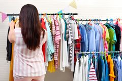 Beautiful overweight woman near rack with clothes Royalty Free Stock Photography