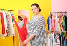 Beautiful overweight woman near rack with small-sized Stock Image
