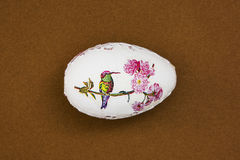 Beautiful painted Easter egg with bird on the brown background Royalty Free Stock Image