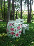 Beautiful painted jar and bench in the garden. Beautiful painted jar and bench in the green garden royalty free stock photos